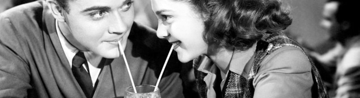 Image from the 1950's of a man and a woman sharing a milk shake in a diner