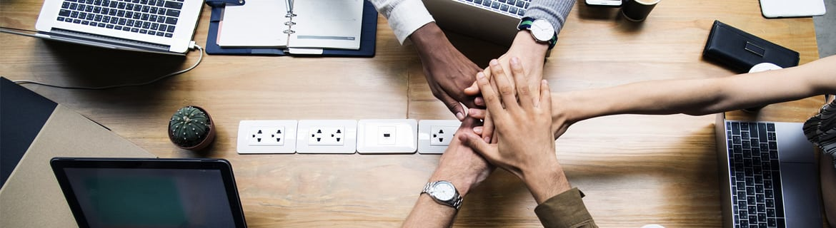 young professionals putting their hands in over a desk