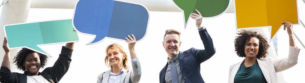 people holding cut out speech bubbles above their heads