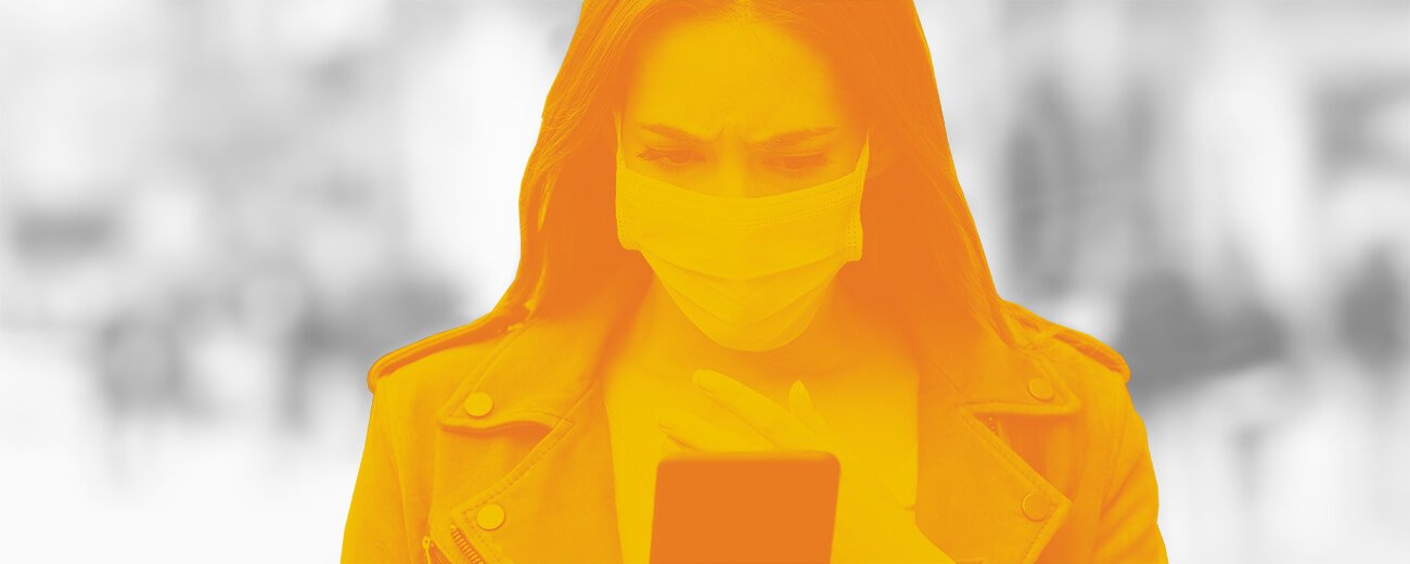 woman looking at mobile phone wearing a surgical mask