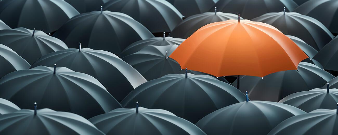 One Orange umbrella in a group of black umbrellas