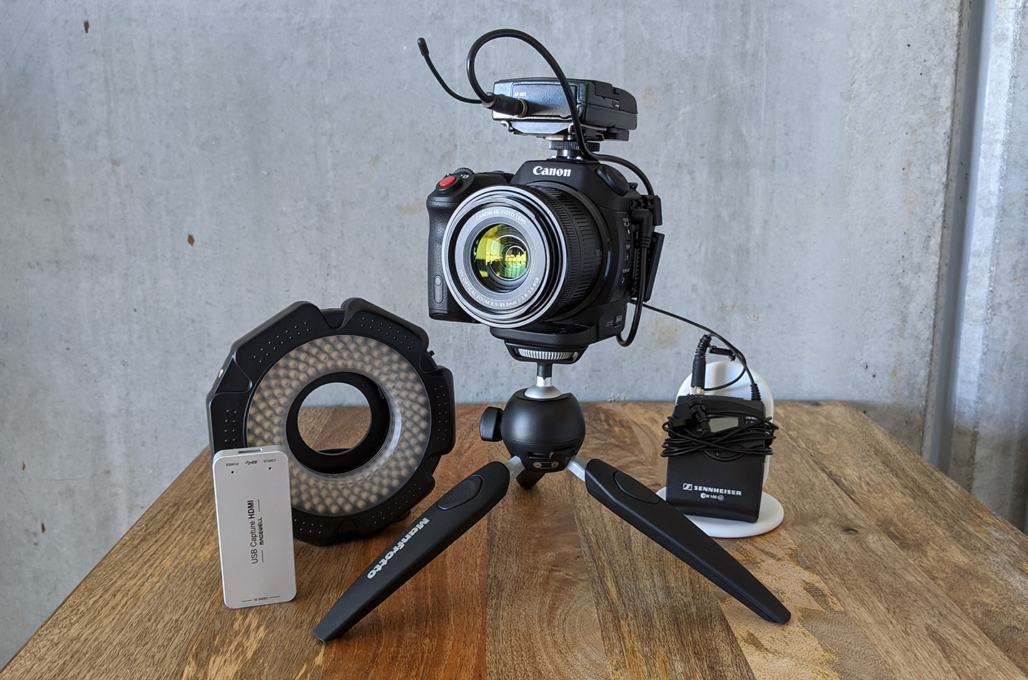 Camera sitting on a small tripod on a table alongside additional video equipment.