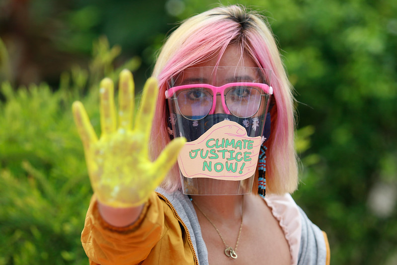 """A woman with a face shield, pink glasses, and blonde hair, holding her hand forward with a yellow glove on and a paper note on the shield saying """"Climate Justice Now!"""""""