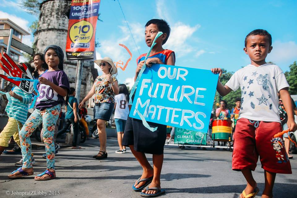"""Several children walking in a march and one holding a blue poster saying """"Our Future Matters"""""""