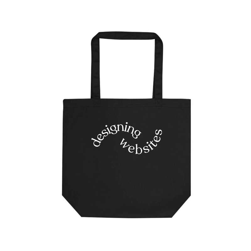 "A black cotton tote bag with curved white text across the middle saying ""designing websites."""