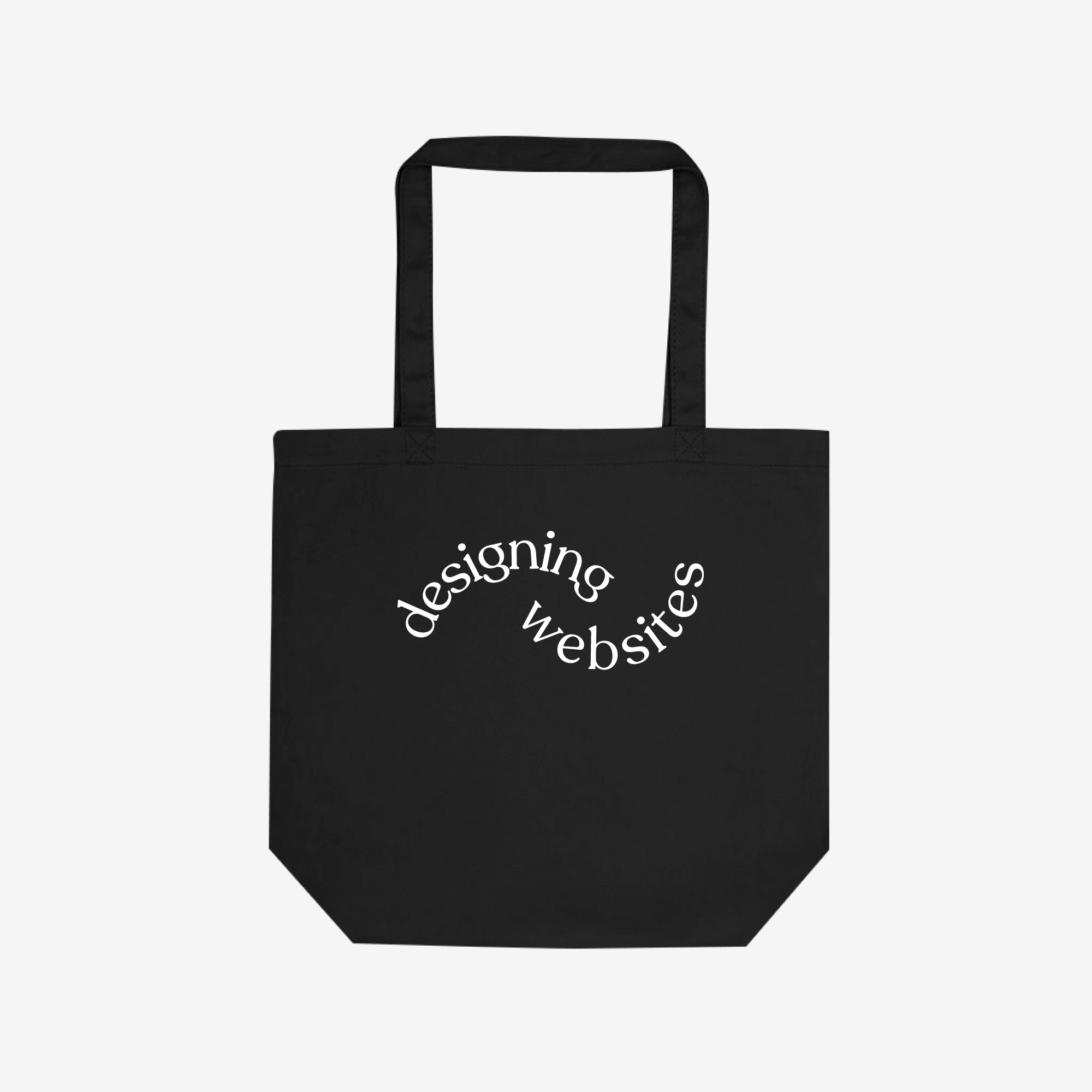 """A black cotton tote bag with curved white text across the middle saying """"designing websites."""""""