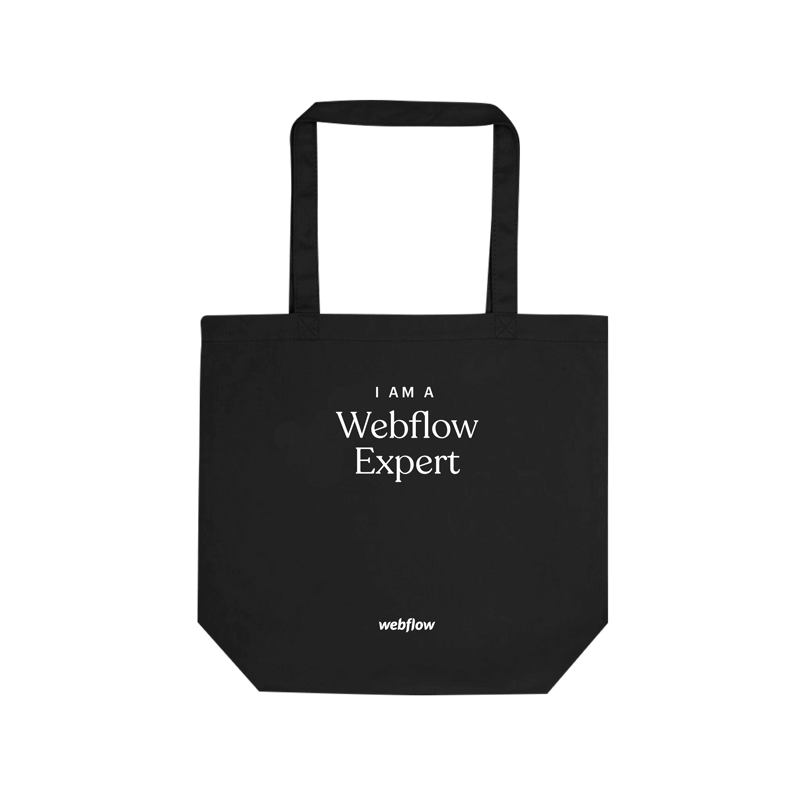 """A black cotton tote bag with curved white text across the middle saying """"I am a Webflow Expert"""" and a small white Webflow logo at the bottom."""
