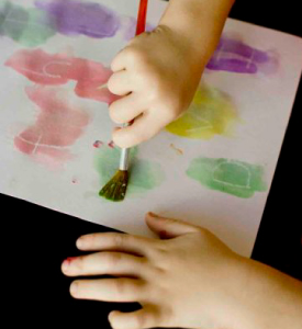 A child colouring white piece of paper with paint.