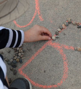 A kid tracing letter B with small stones.