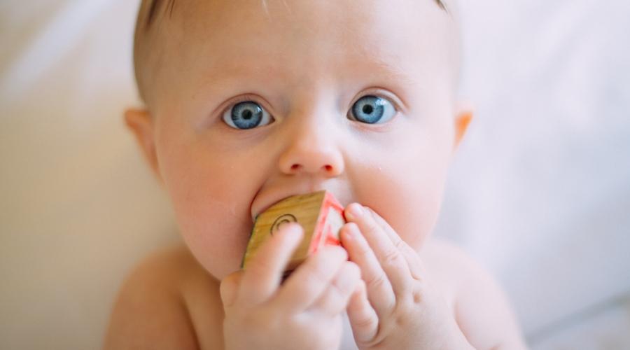 infant eating wooden alphabet block
