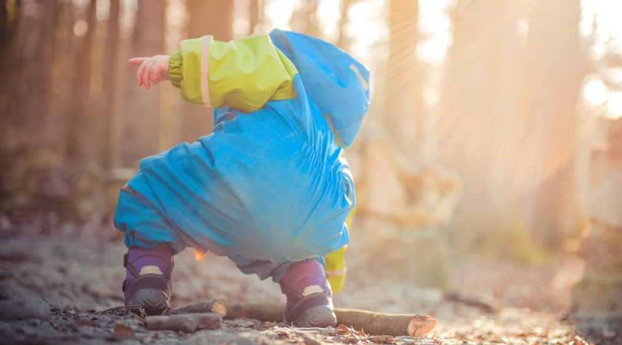 child bends down in woods to grab stick
