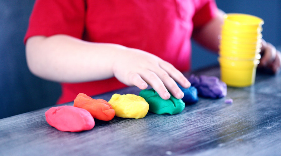 toddler's hands playing with rainbow playdough