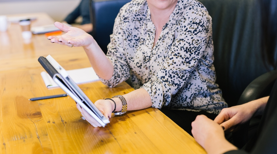 woman holding notepad and gesturing right hand