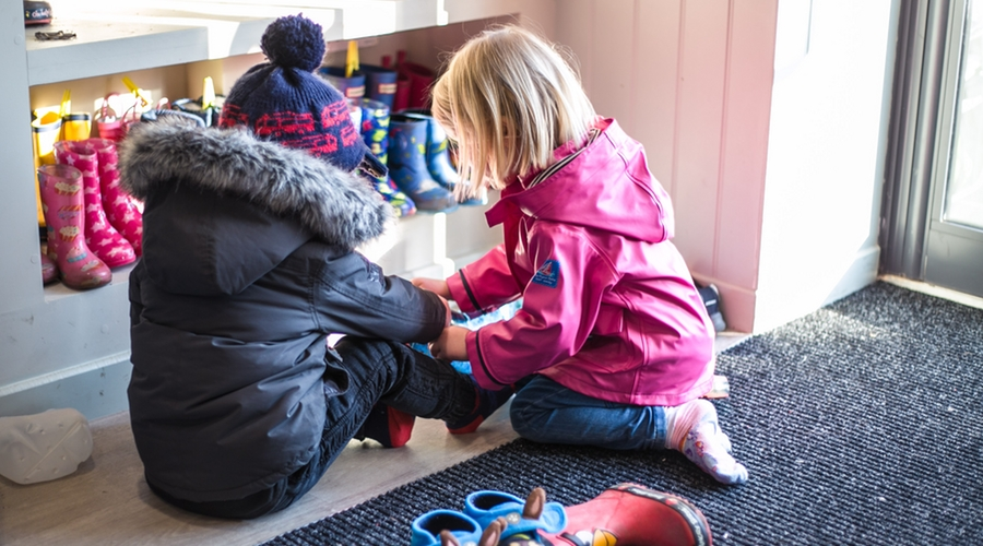 little girl in pink jacket helping boy put shoes on