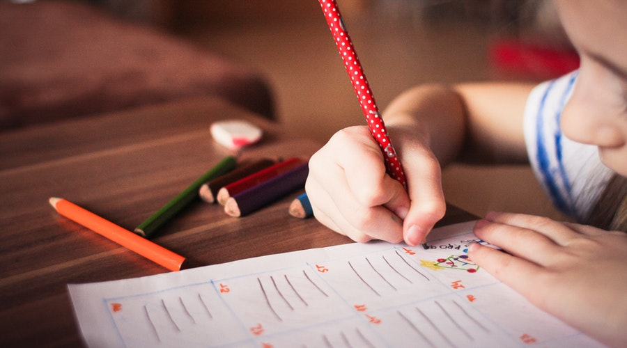 girl writing with red polka-dot pencil