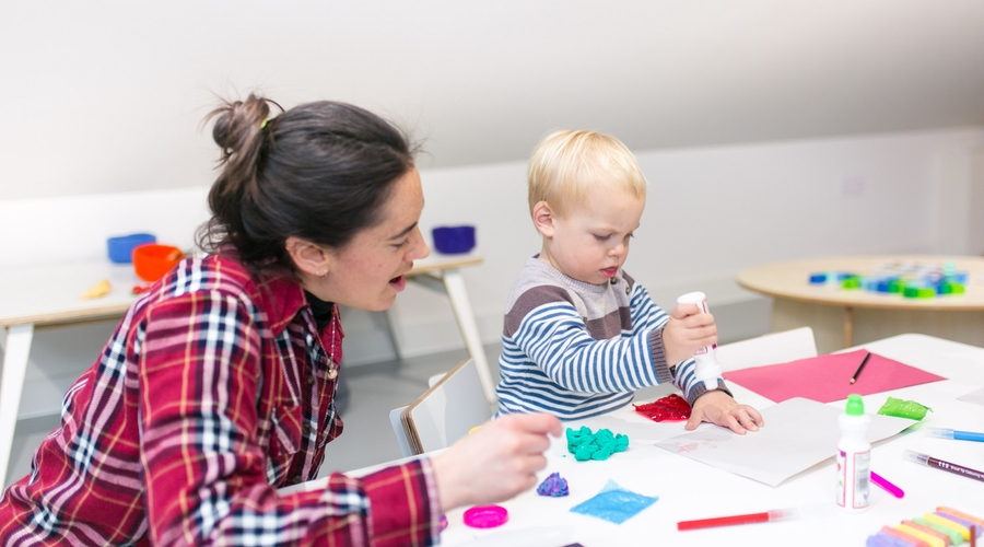 Adult helping toddler glue paper
