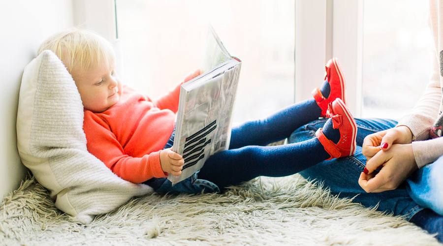 toddler with red shoes reading book