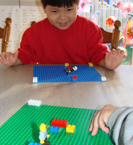 A boy playing with Lego bricks