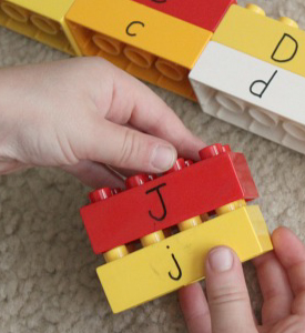 Kid's hands holding Lego bricks