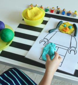 Outline of lego man filled with play dough
