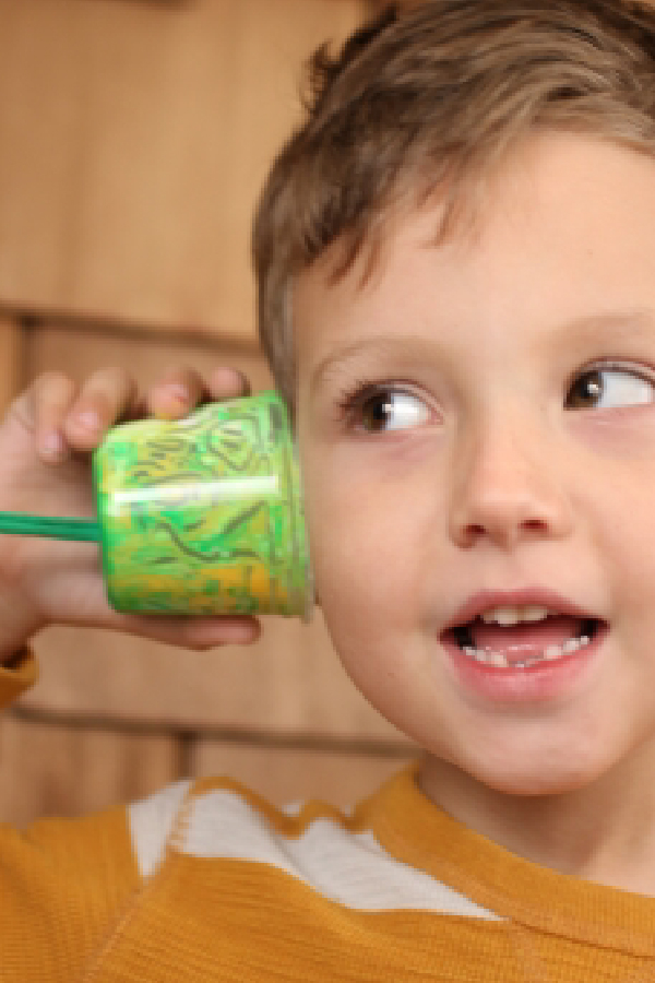 Picture of a boy listening to paper cup telephone.