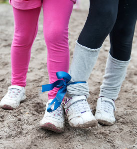 Two kids with legs tied with a bow