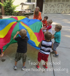 A group of kids playing with a parachute