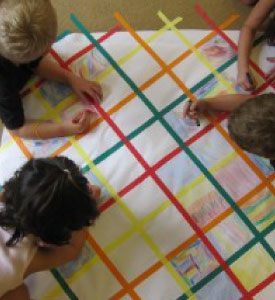 Kids colouring a sheet of paper on the floor