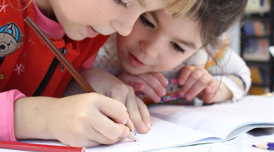 two young girls drawing with brown pencil