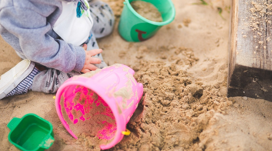 toddler playing with sand and pink bucket