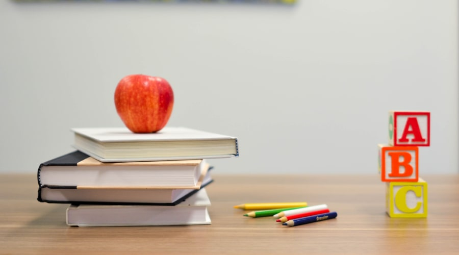 apple and books sitting on desk