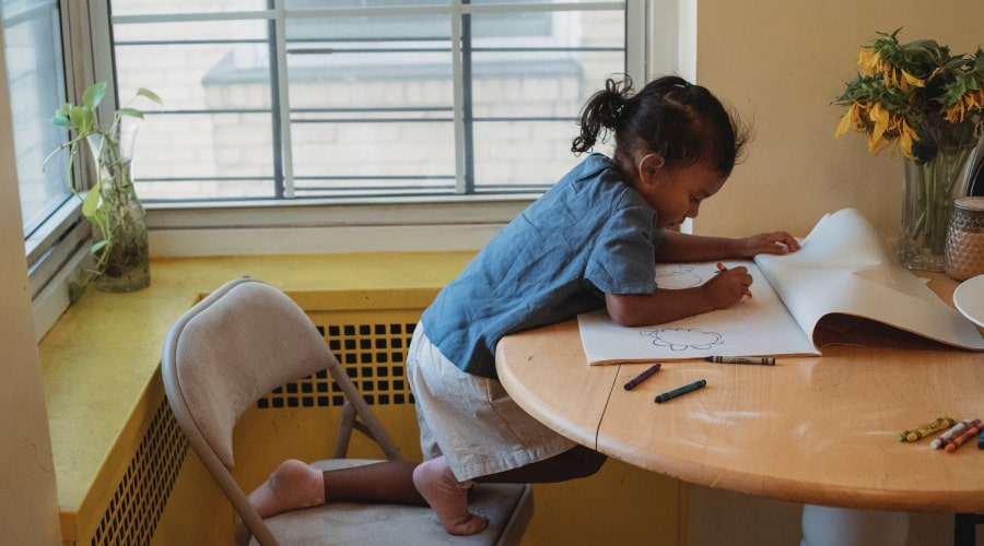 child leaning over table colouring with crayons