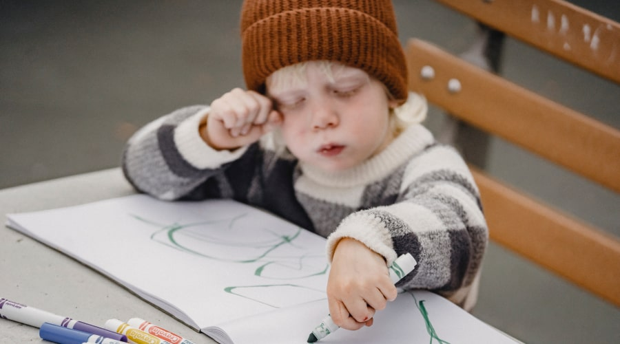 blonde child in brown hat drawing with green pen