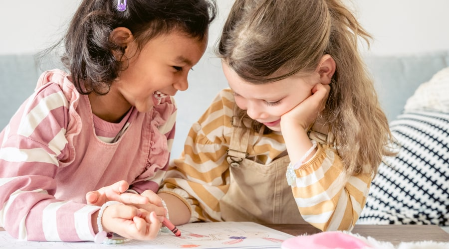 two girls laughing and colouring with crayons