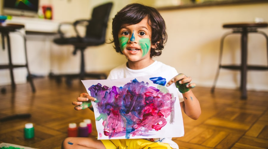 child with face paint holding up finger painting