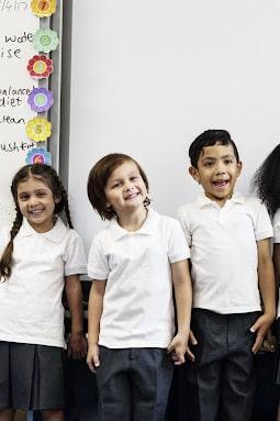 three children in white polos smiling