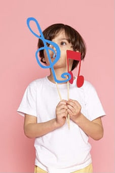 boy holding colourful musical notes