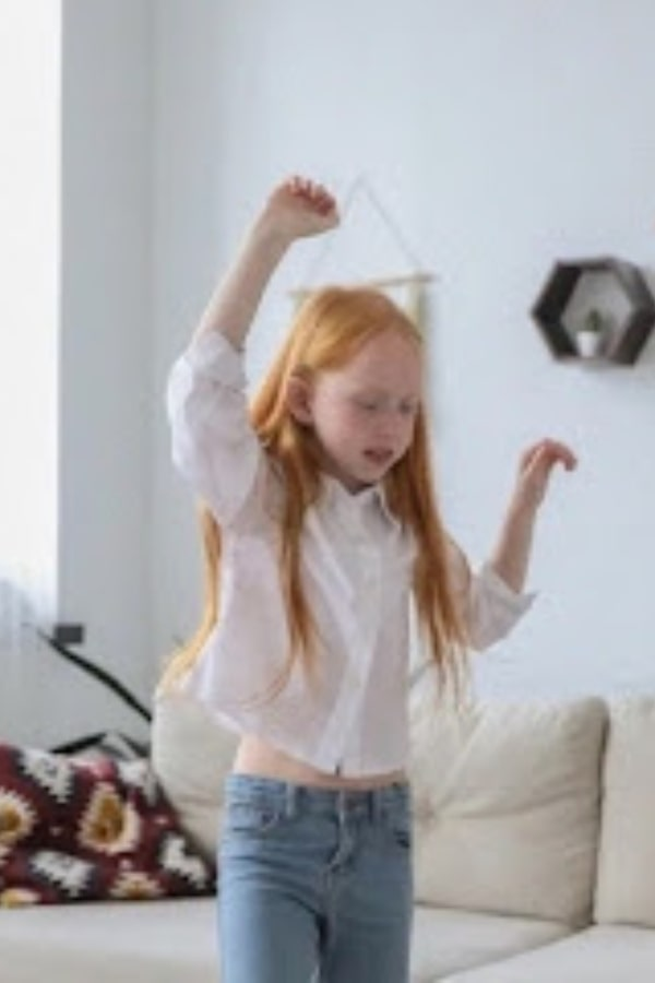 girl with red hair dancing with arms in air