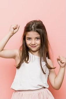 brunette girl dancing with hands in air