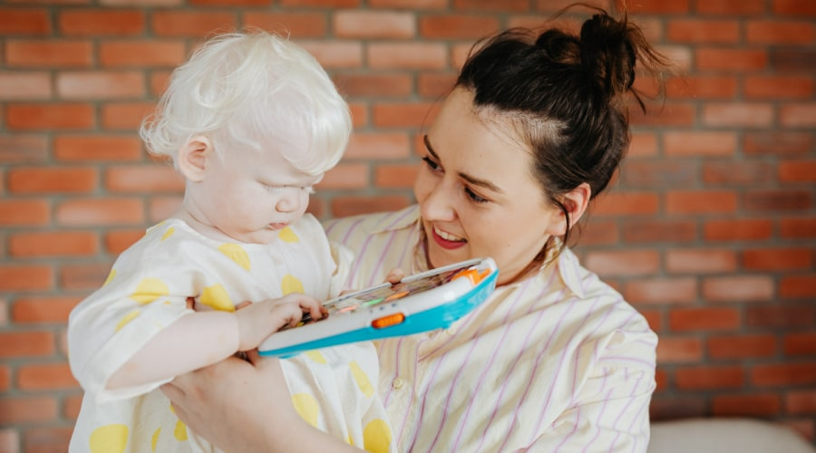 woman holding baby playing with toy