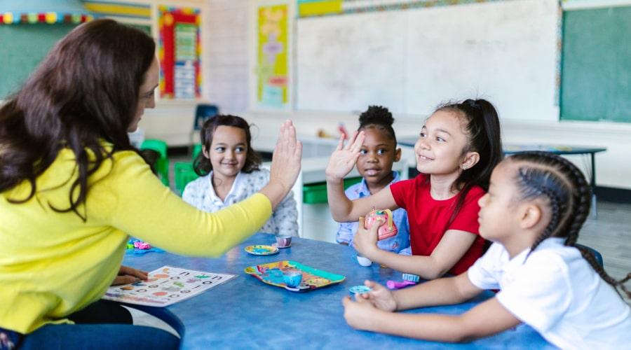 A teacher and a girl doing a high five