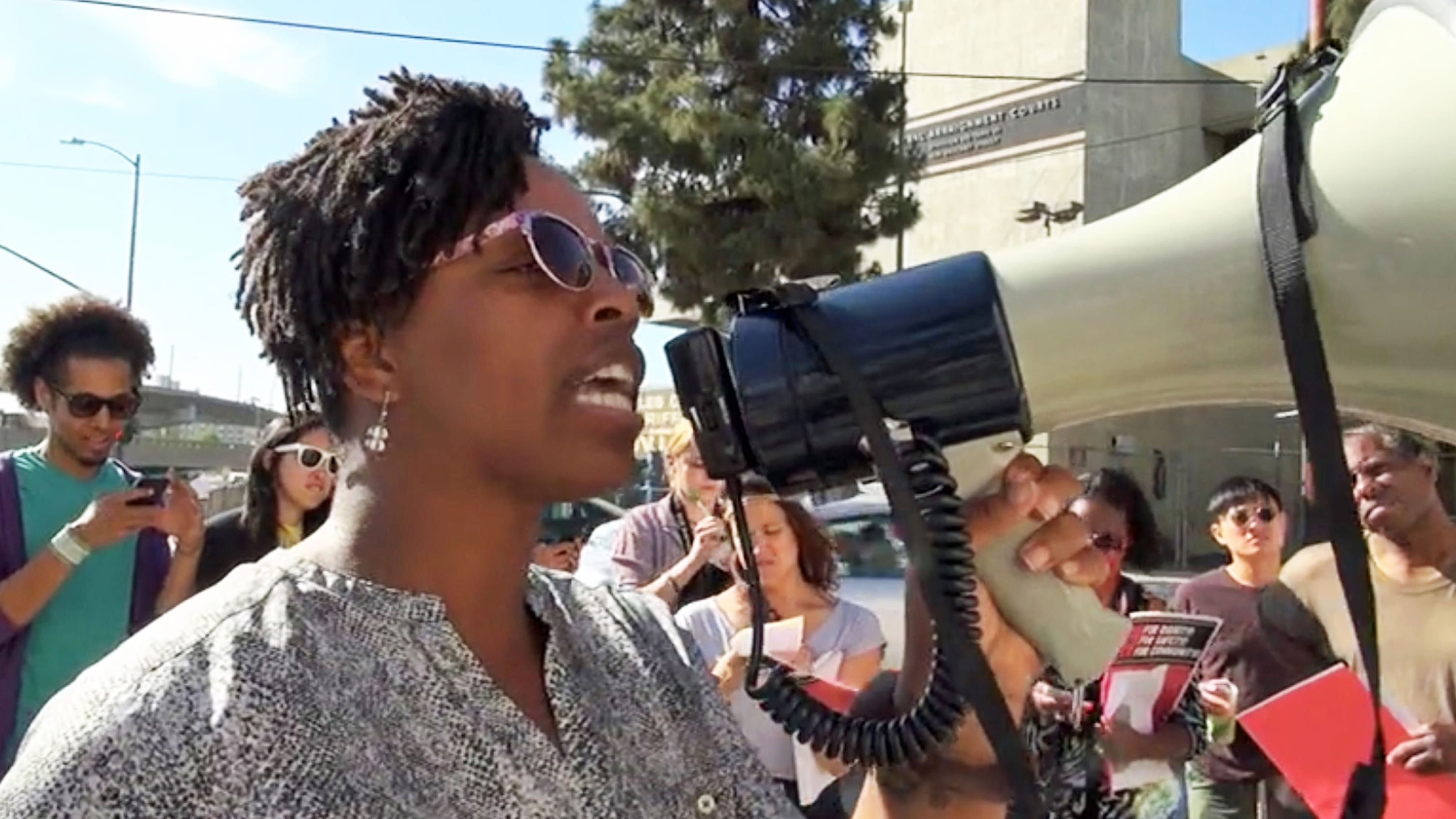 A black woman leads a protest with a loudspeaker