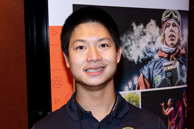 Alex Chau of MOPD smiles in front of a ReelAbilities poster