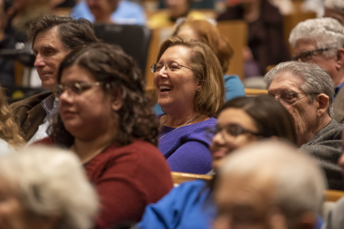 a woman in a crowd at a ReelAbilities event laughs