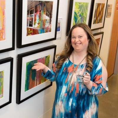 A Celebration Company artist proudly displays her work