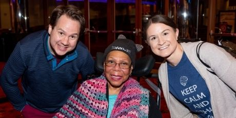 Two young adults pose for a picture with a African American woman using a wheelchair