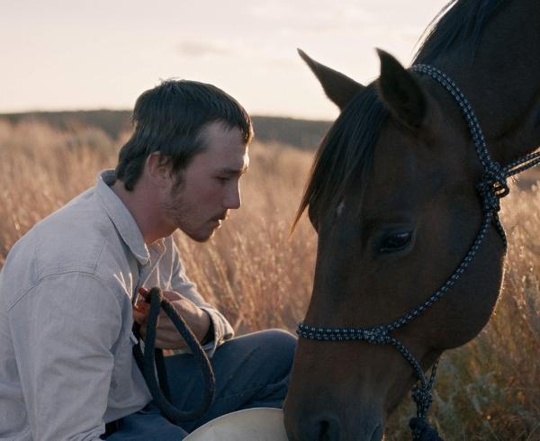 Brady Jandreau, star of the Rider, with a dark chesnut horse