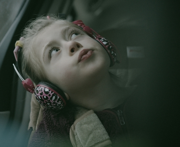 A young girl wears noise canceling headphones while riding in a car