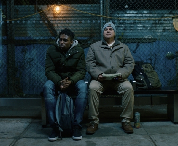 Tereek and Artie sit on a bench near a bus stop in New York City