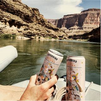 Two people cheersing Superbird Palomas with the Grand Canyon in the background.